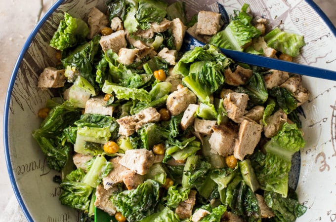 Overhead photo of a ceasar salad with chikcne and chick peas in a bowl with caesar dressing and wooden salt and pepper shakers off to the side