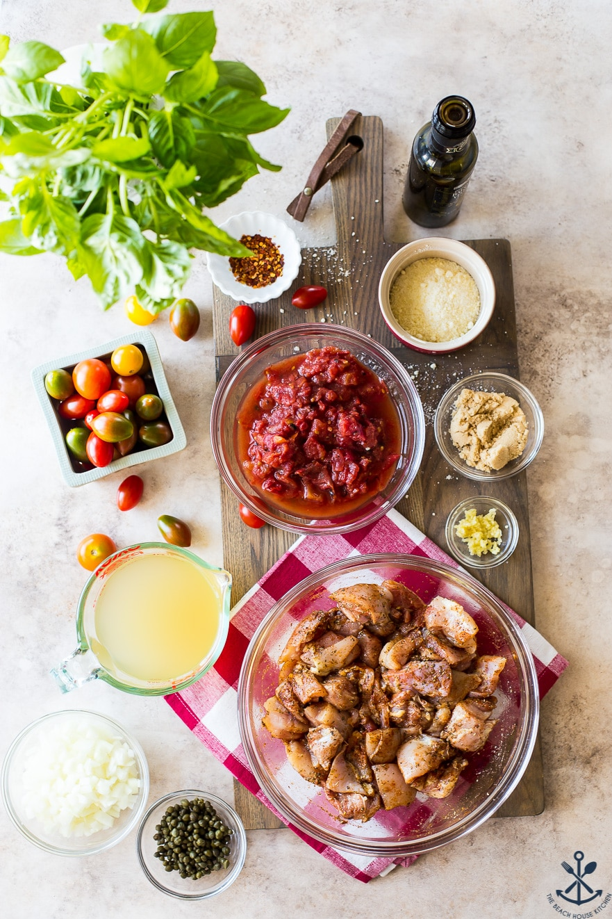 Overhead photo of ingredients for chicken dish in glass bowls on a wooden board