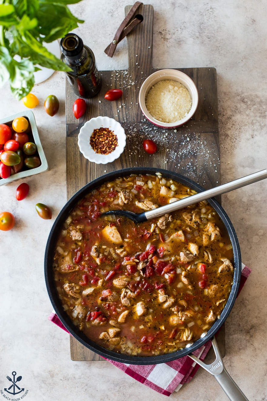 Overhead photo of skillet filled with beef broth, chicken, orzo and tomatoes