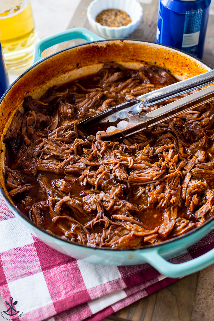 A dish of beer-braised bbq chuck roast with a pair of silver tongs