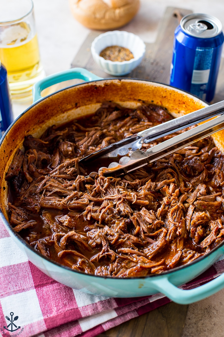 Shredded BBQ chuck roast in a baking dish with a set of silver tongs