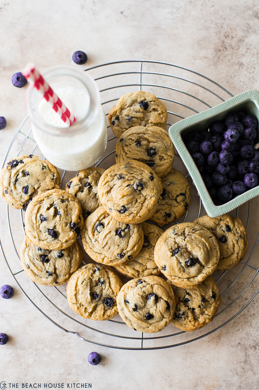 Overhead photo of cookies on a round wire rack with a bottle of milk and a basket of blueberries