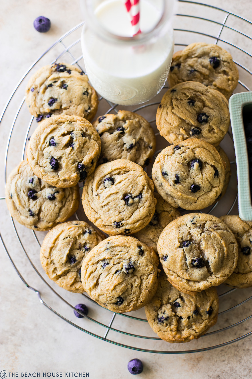 Overhead photo of cookies on a round wire rack with a bottle of milk