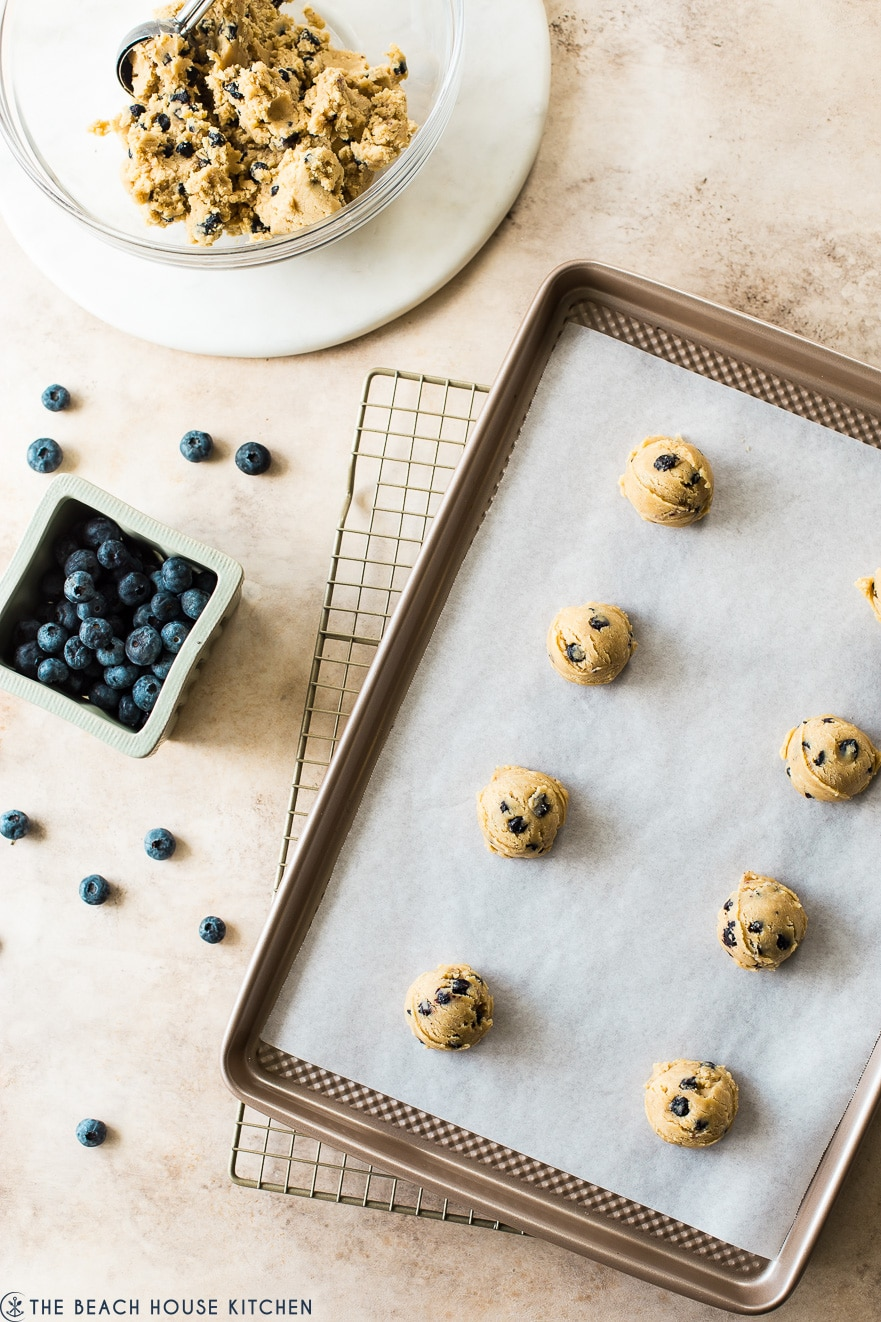 Overhead photo of pre-baked cookies on a parchment lined sheet with a bowl of cookie dough and a basket of blueberries off to the side