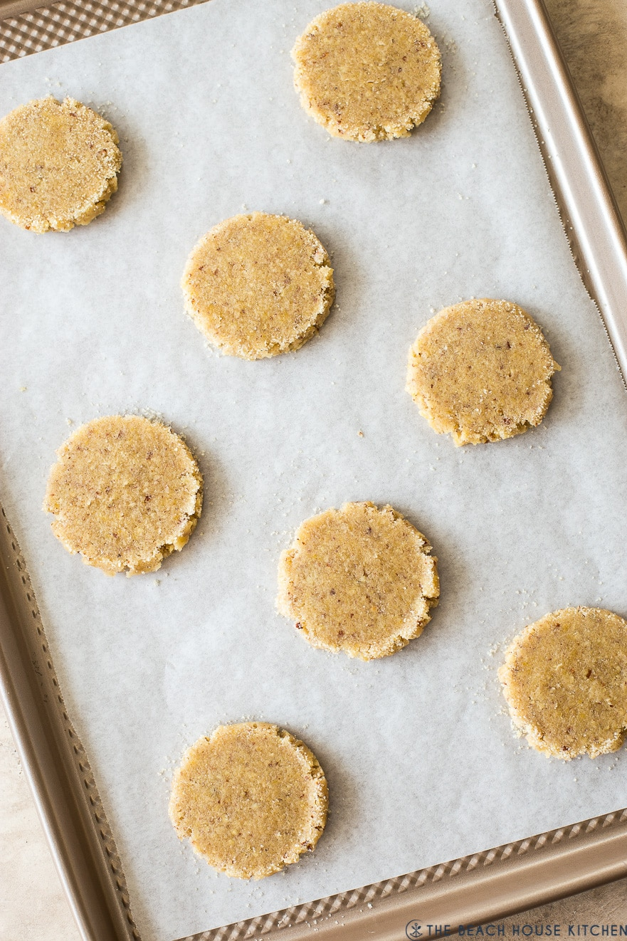 Overhead photo of pre-baked pecan sandie cookies on a parchment lined baking sheet