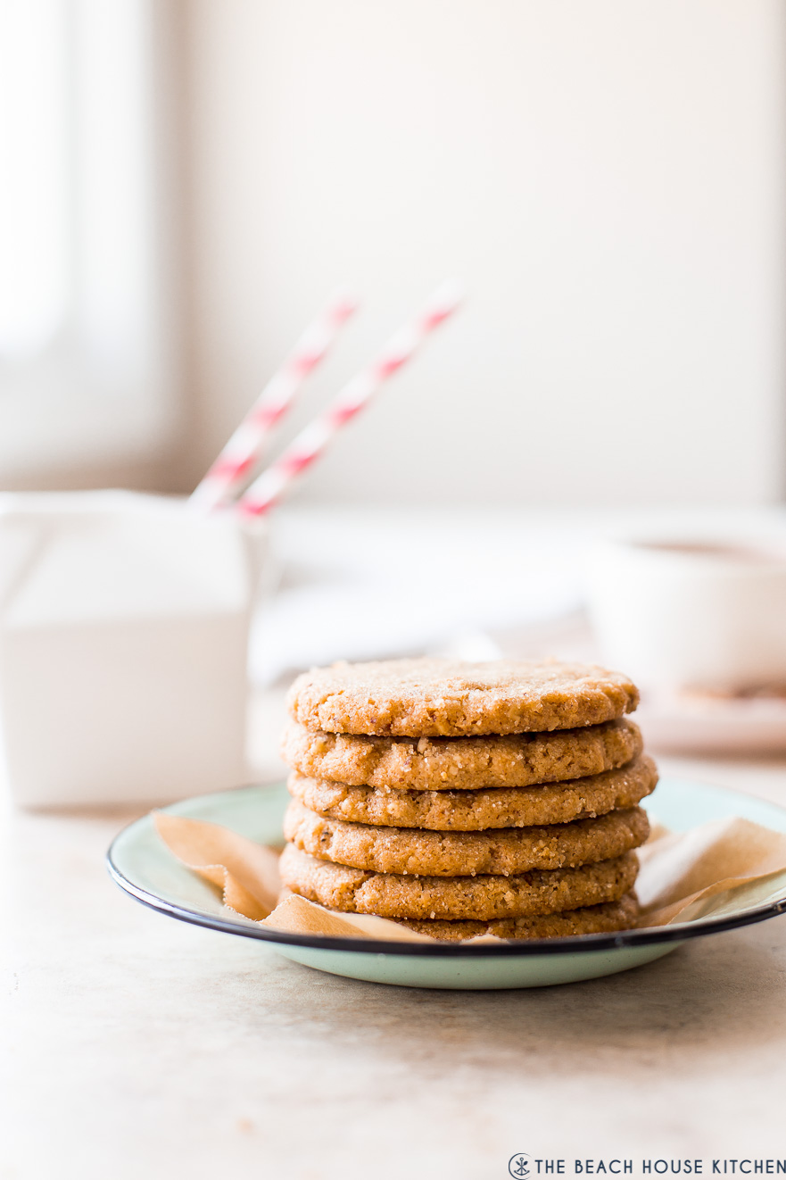A plate with a stack of pecan cookies with a small caron of milk in the background