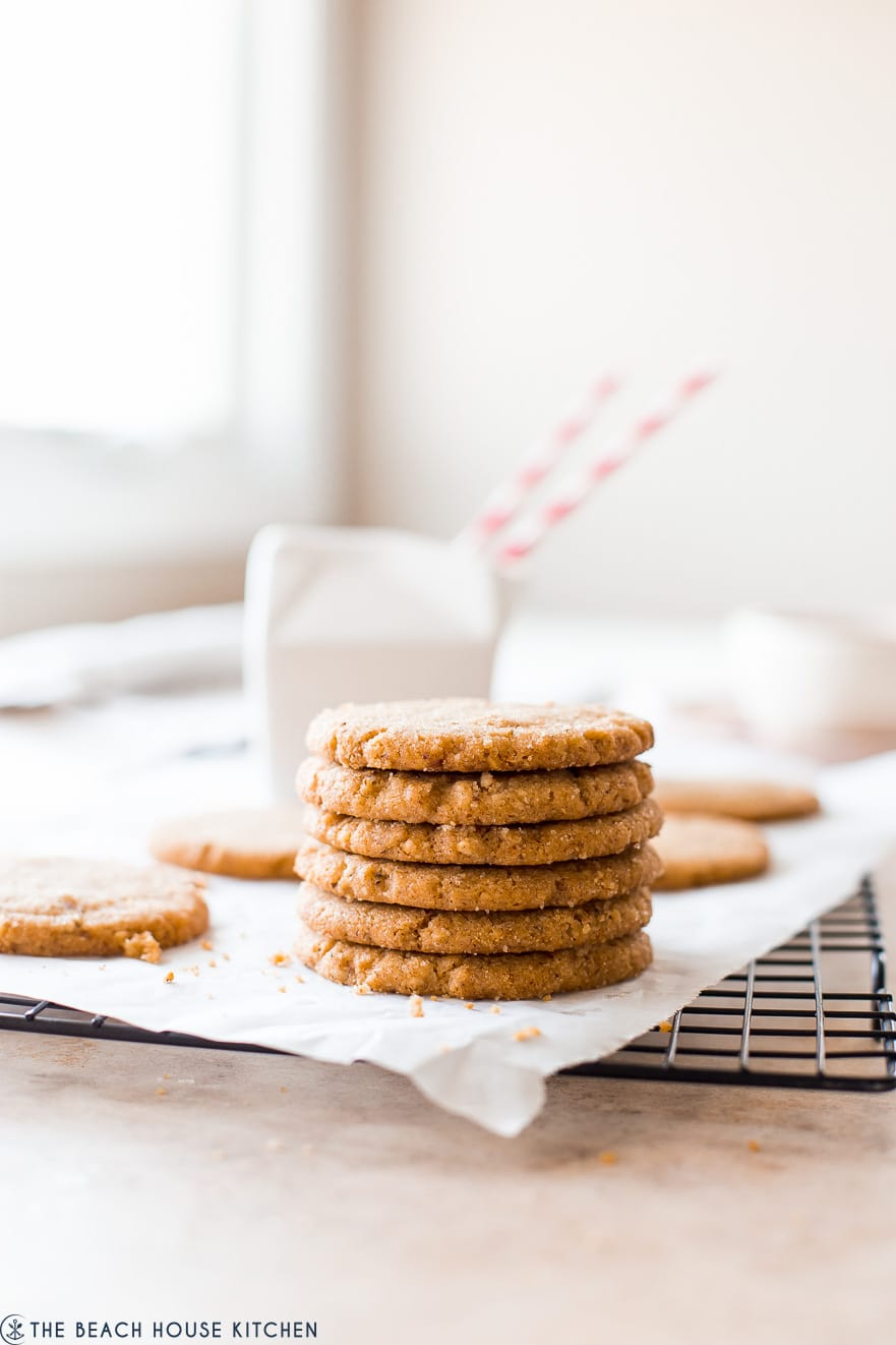 A stack of pecan cookies on a sheet of white parchment on a wire rack