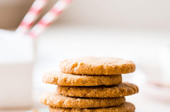 Up close photo of a stack of pecan sandie cookies on a plate