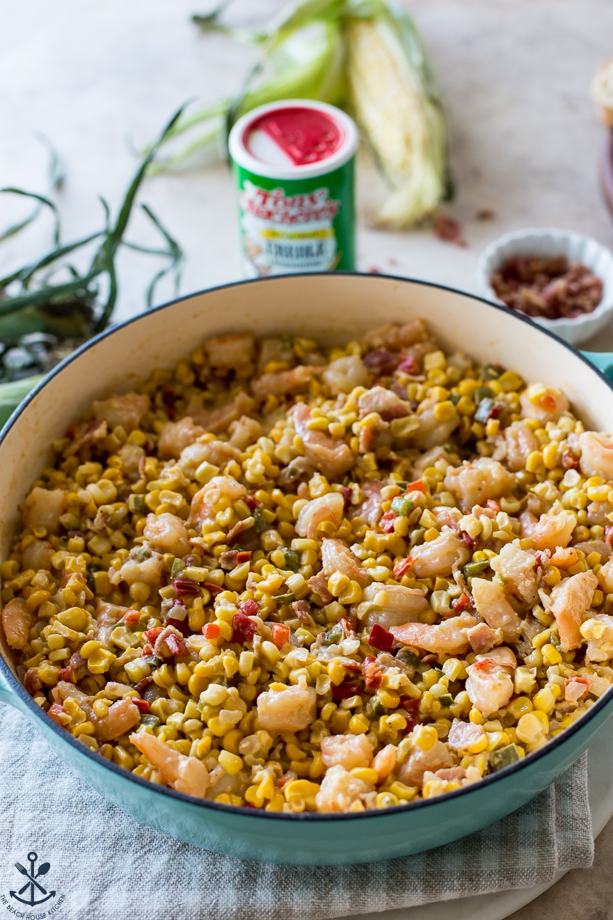 A baking dish filled with corn maque choux with shrimp