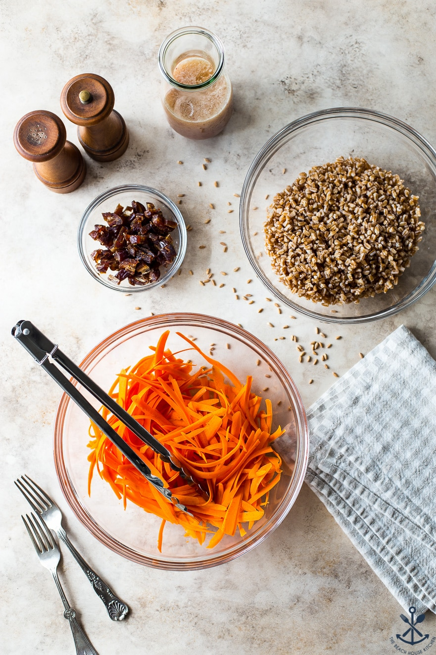 Overhead photo of a bowl of shredded carrots, a bowl of farro and a bowl of dates
