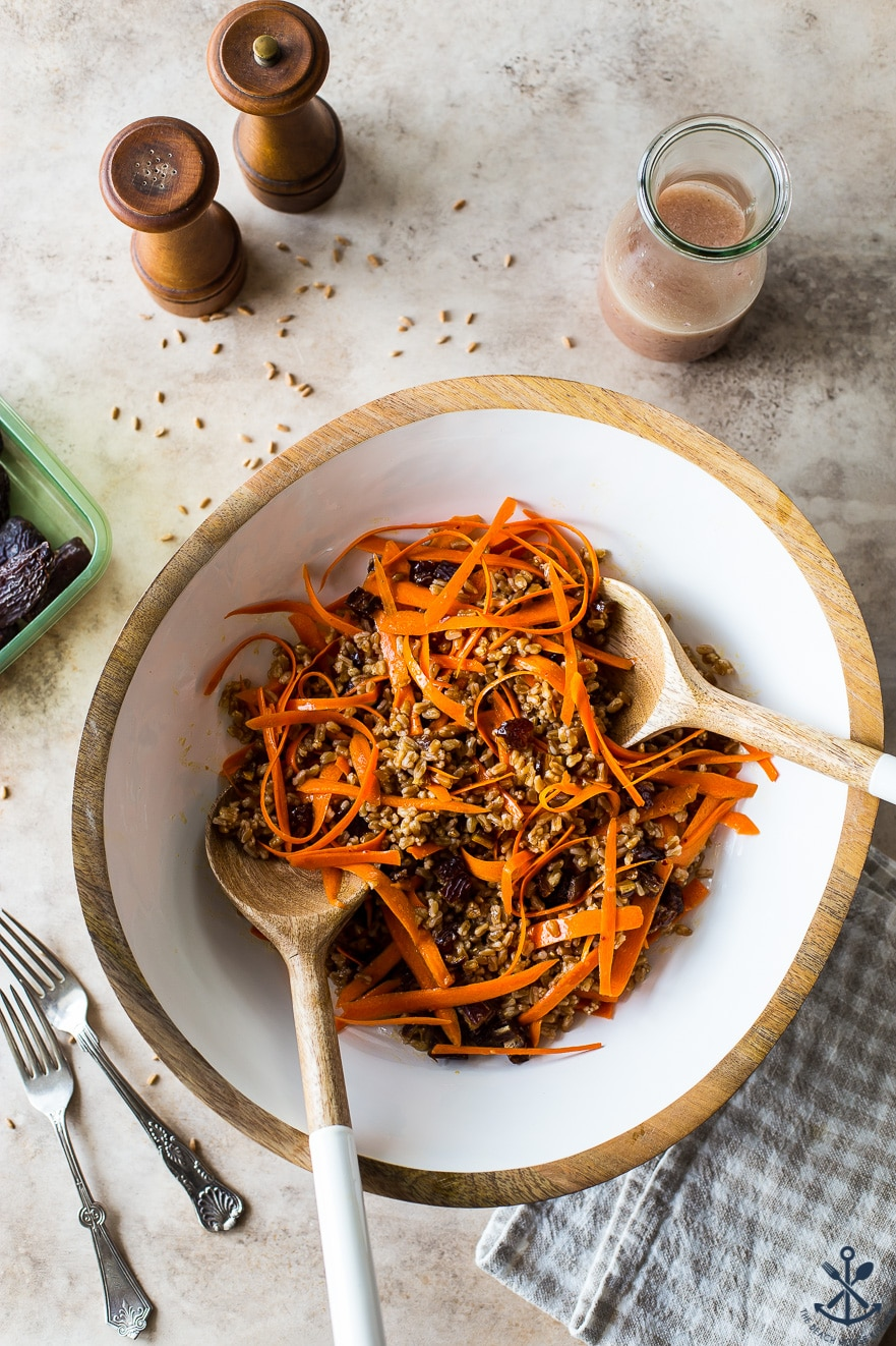 Overhead photo of carrot farro salad with dates and maple vinaigrette in a white bowl with utensils and a bottle of dressing and salt and pepper shakers off to the side