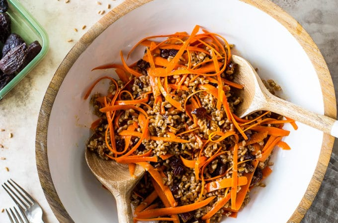 Overhead photo of a carrot salad in a white bowl