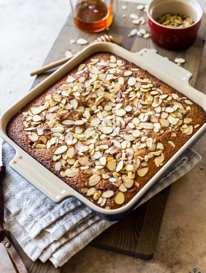 Easy Spiced Honey Snack Cake topped with almonds in a square baking pan