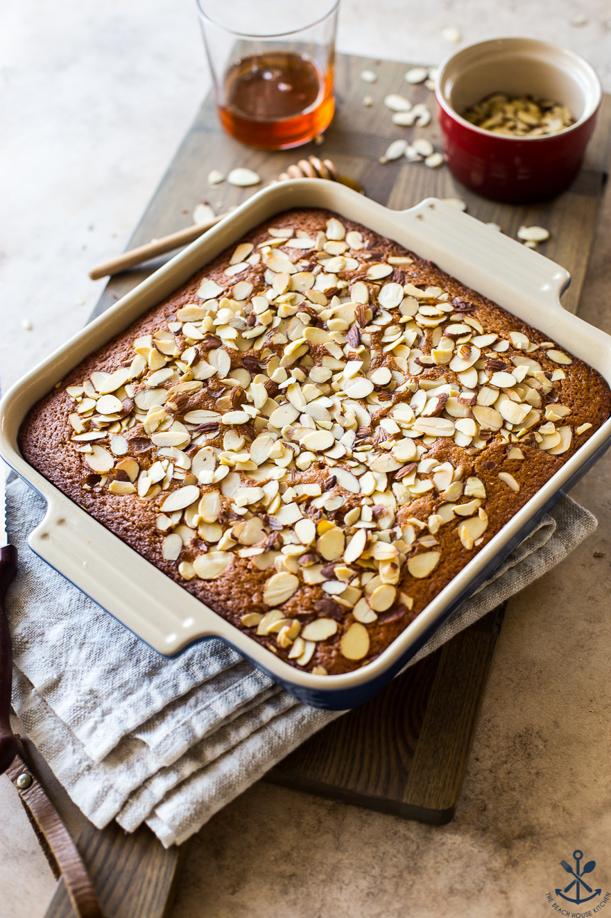 A cake topped with sliced almonds with a glass of honey and a small red dish of almonds in the background