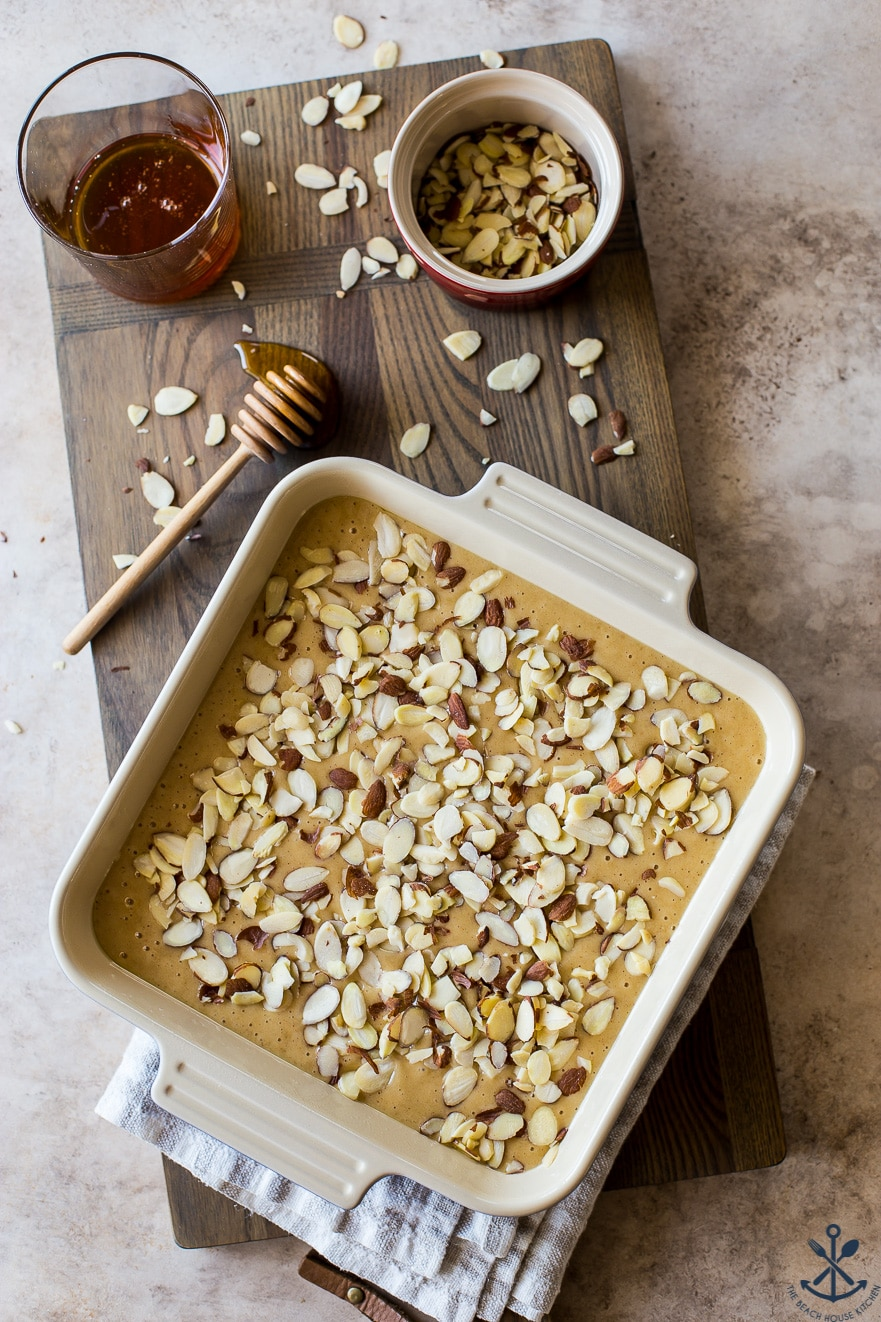 Overhead photo of a pre-baked cake topped with almonds in a square pan