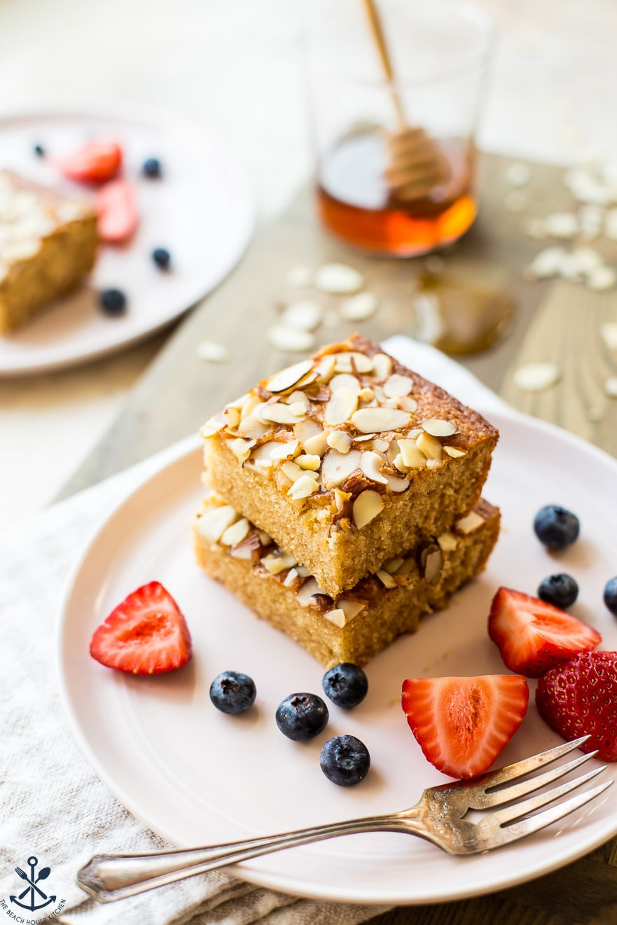 A stack of two slices of easy spiced honey snack cake on a pink plate with strawberry slices and blueberries