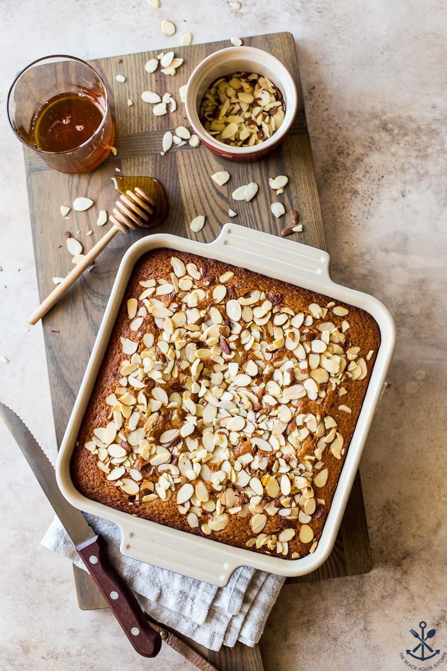 Overhead photo of a square baking pan with a cake topped with sliced almonds