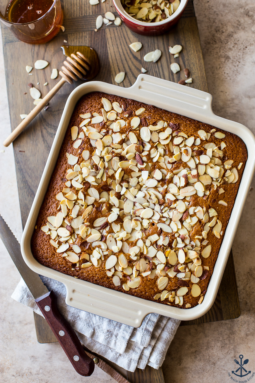 Overhead photo of a honey spiced snack cake topped with almonds in a square pan