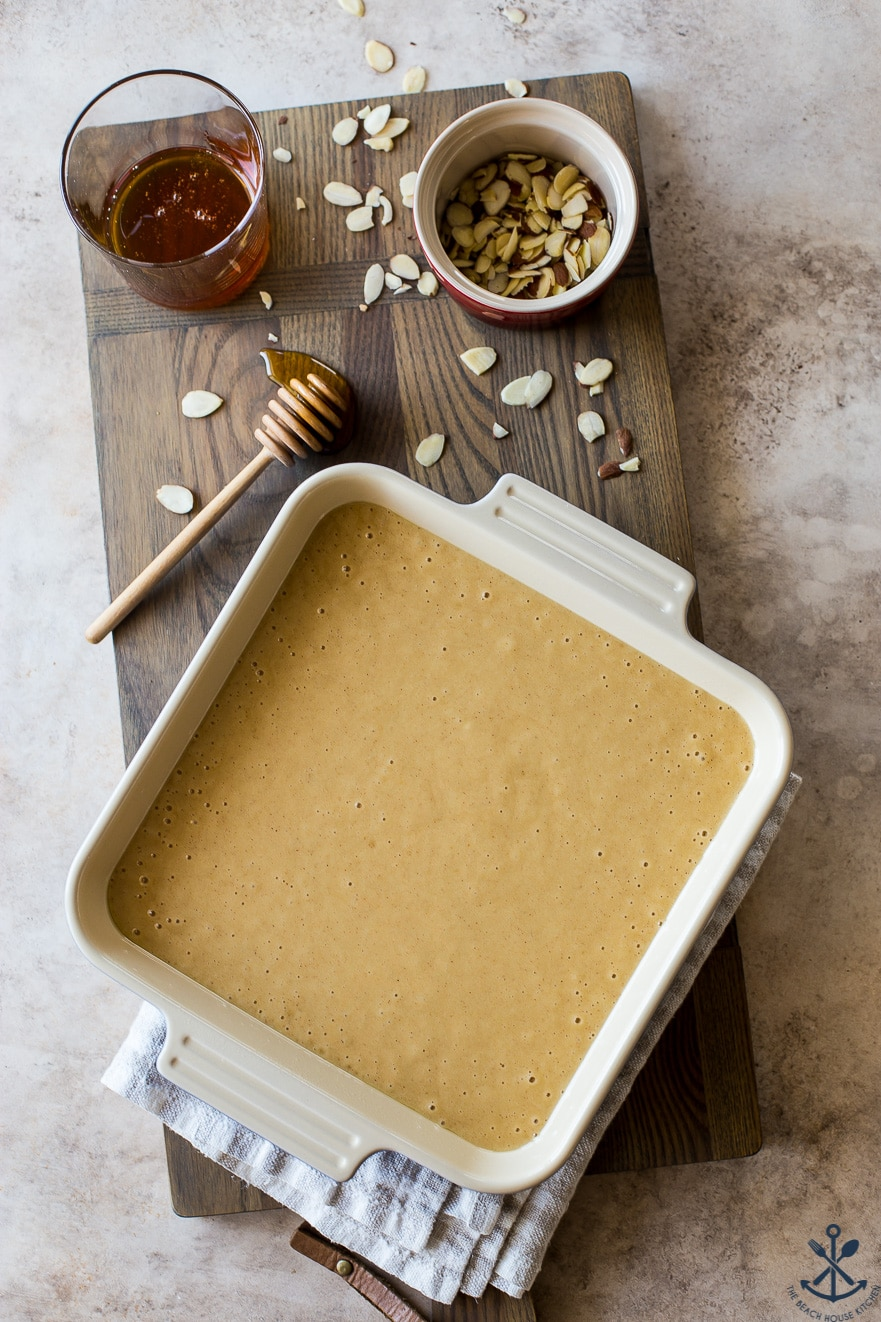 Overhead photo of batter for a cake in a square pan on a wooden board