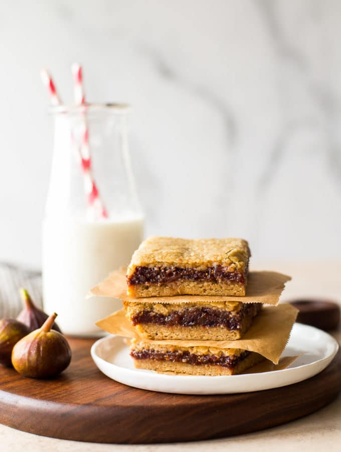 A stack of three fig bars on a white plate with a bottle of milk in the background