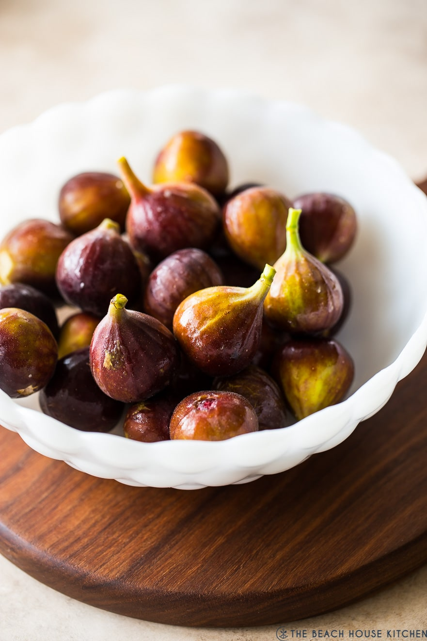 A white bowl of figs on a wooden board