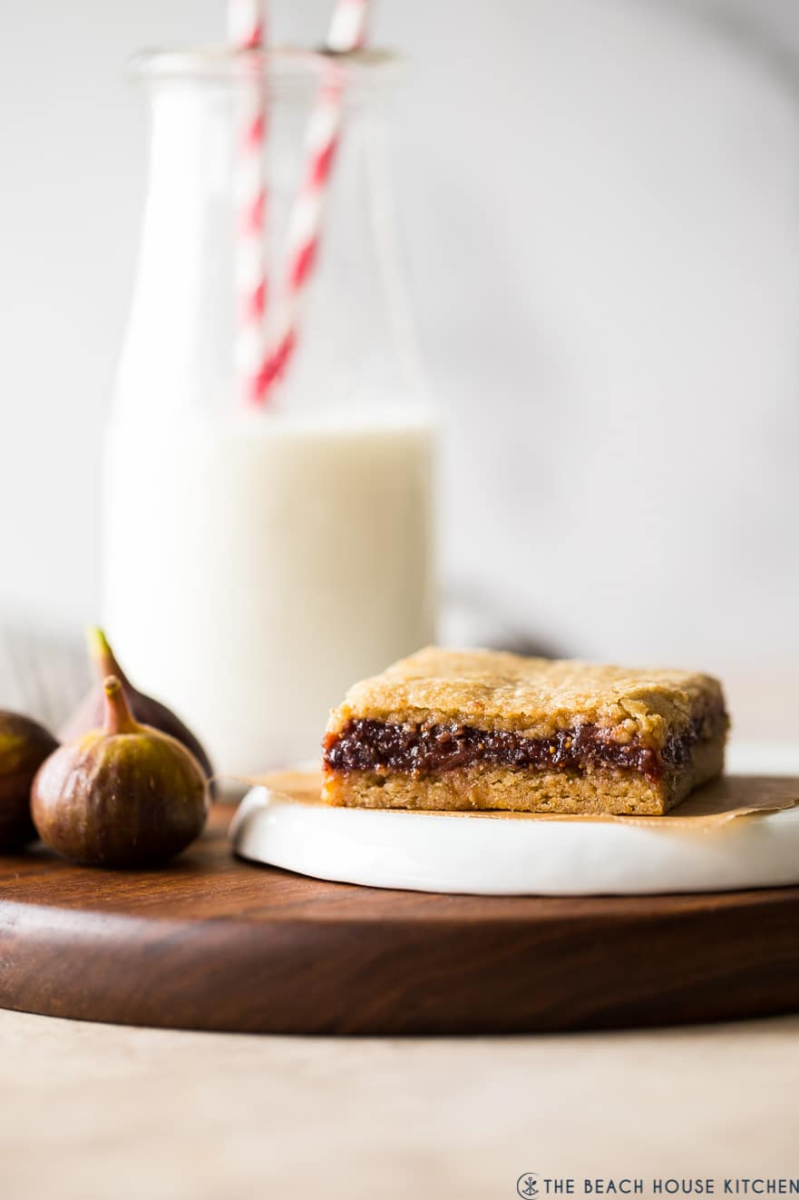 Up close photo of a fig bar on a wooden board with a bottle of milk behind it