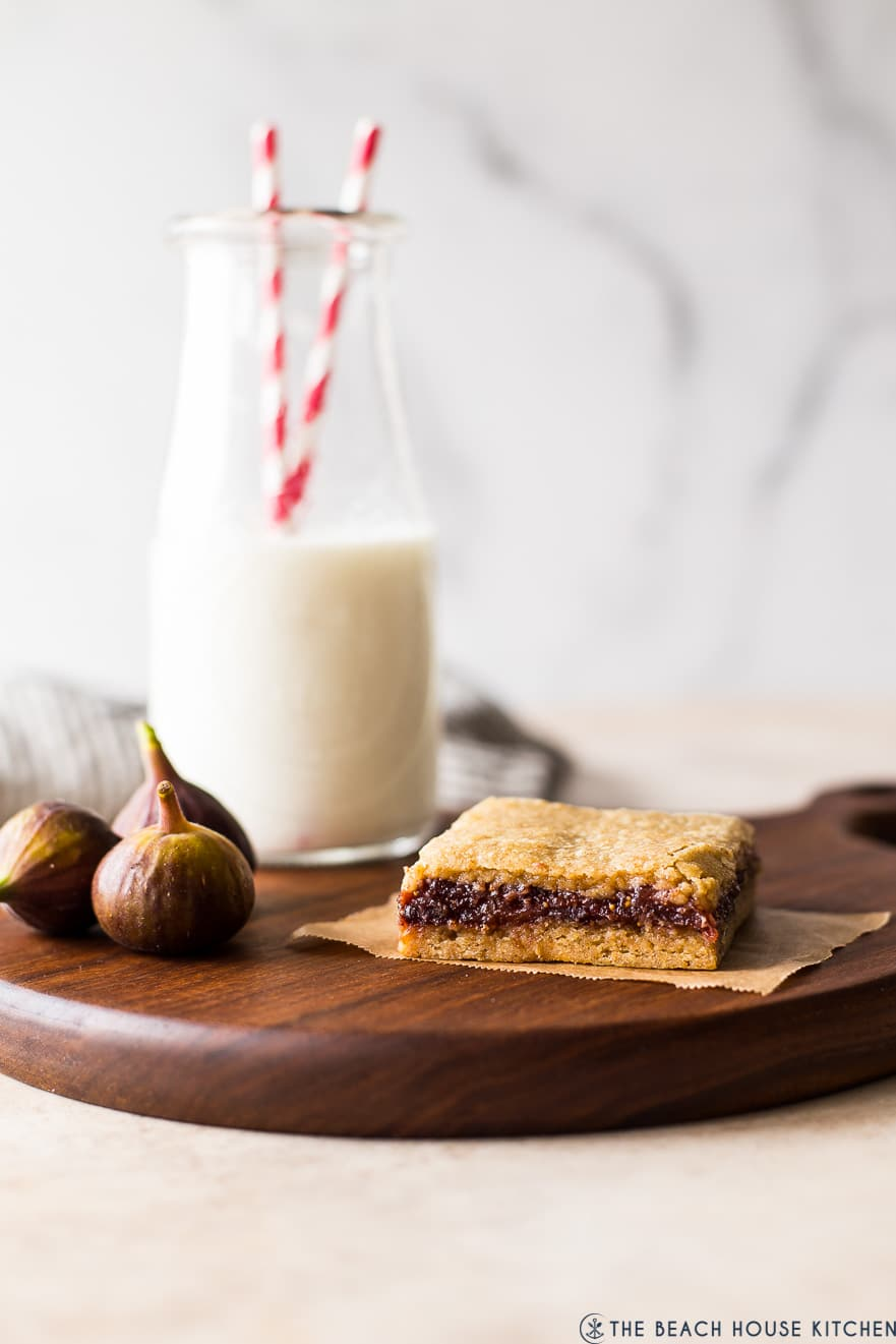 A fig bar on a wooden board with figgs off to the side and a bottle of milk in the background