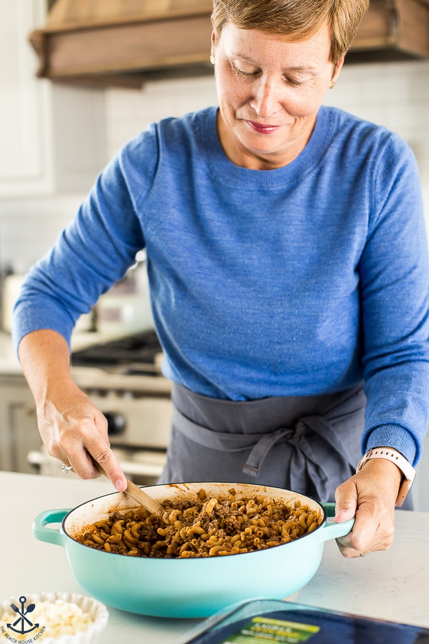 Woman in a bright blue sweater stirring a skillet of beef and pasta