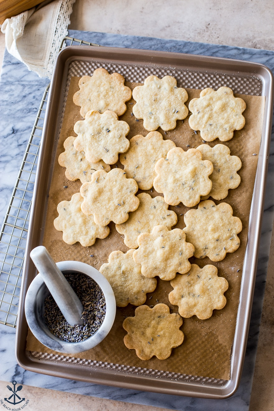 Overhead photo of cookies on a baking sheet with a bowl mortar and pestle filled with lavender