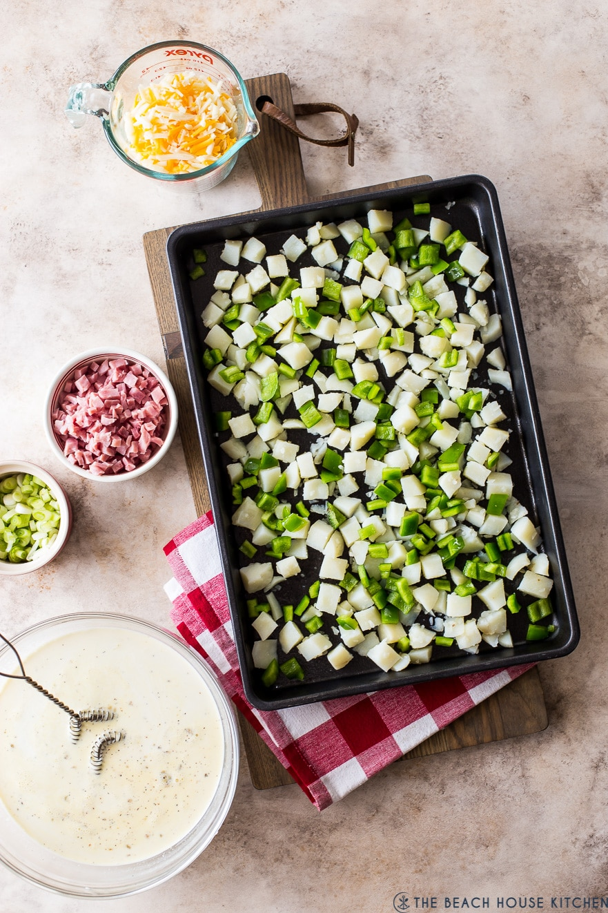 Overhead photo of sheet pan with cubed potatoes and green peppers with other bowls filled with denver omelette ingredients