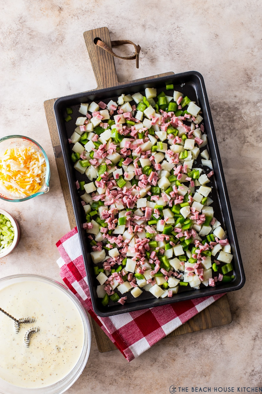 Overhead photo of a sheet pan of cubed potatoes, green peppers and ham