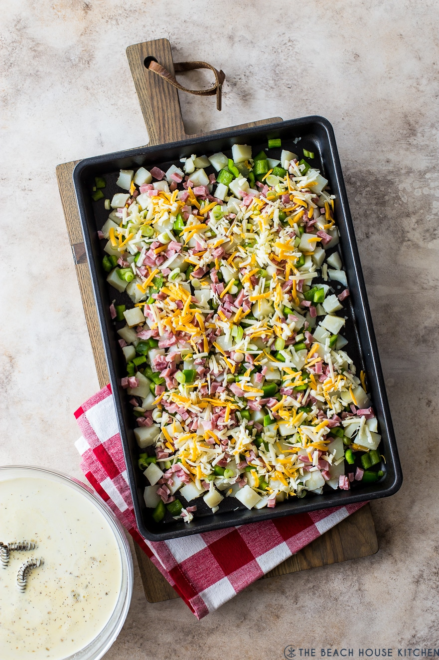Up close overhead photo of a sheet pan filled with cubed potatoes, green peppers, ham and shredded cheese