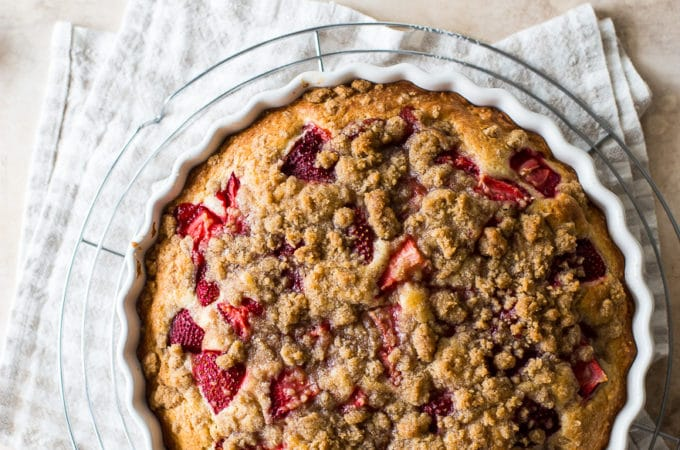 Up close overhead photo of a strawberry buckle in a round white baking dish.