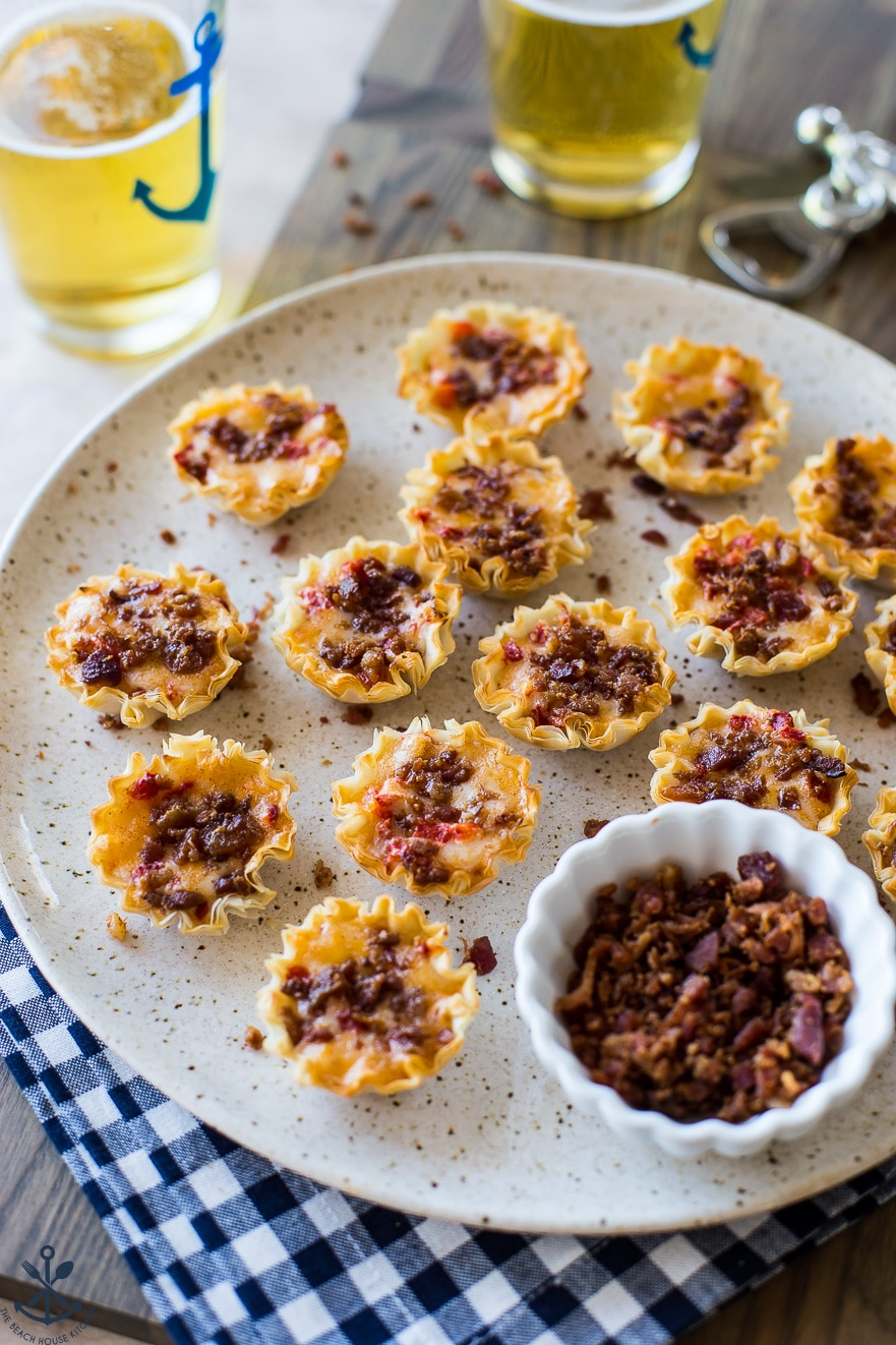 A plate of bacon pimeto cheese bites on a plate with a small bowl of bacon bits