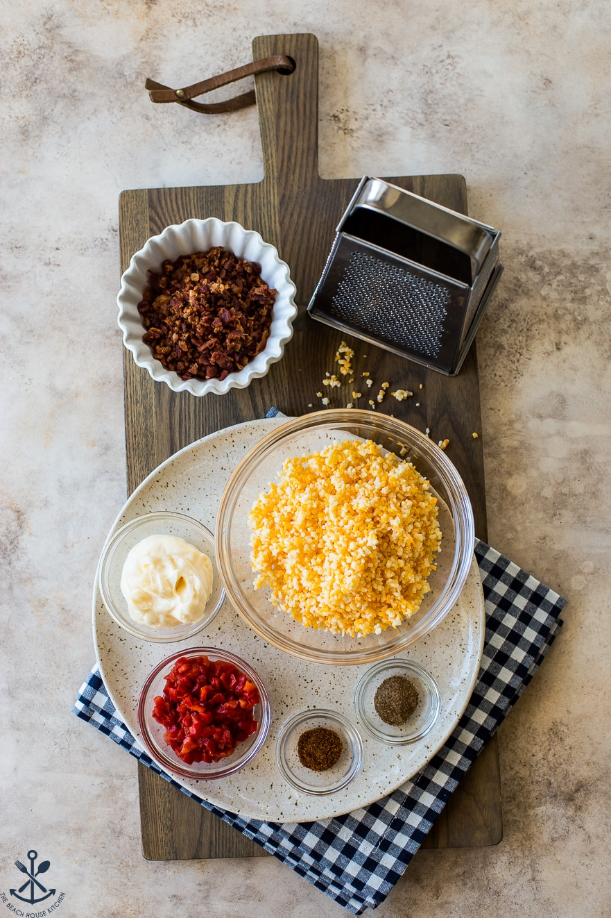 Overhead photo of ingredients for bacon pimento cheese bites on a wooden board with a grater