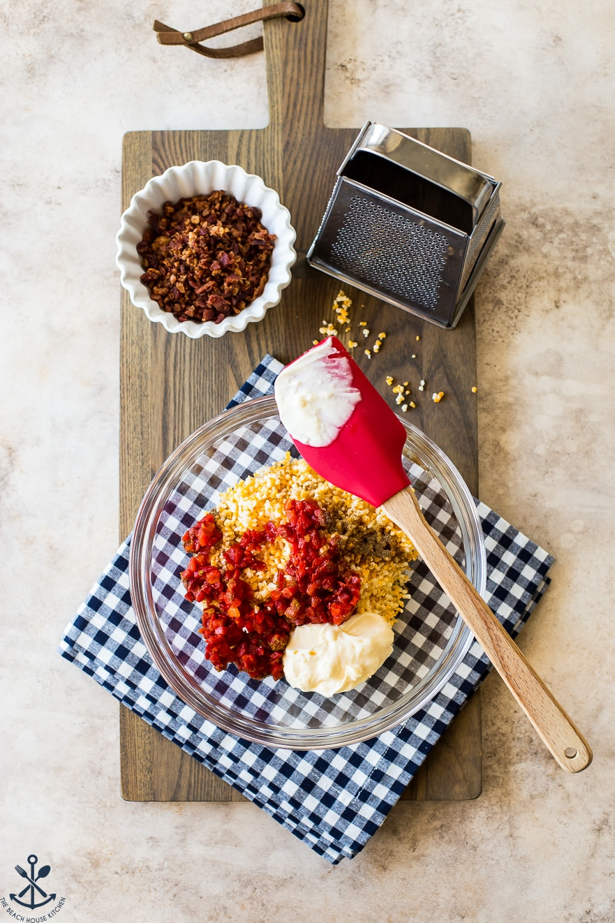 Overhead photo of a bowl with pimento cheese ingredients with a small bowl of bacon and a grater all on a wooden board
