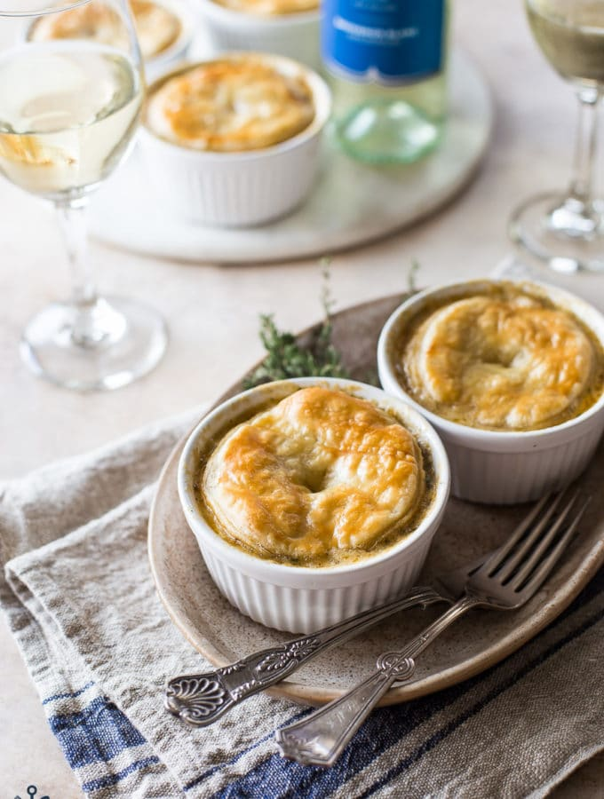 Two chicken pot pies on a brown oval plate with two forks with a bottle of wine and wine glasses in the background