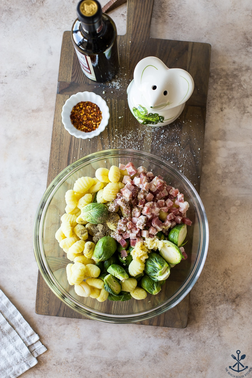 Overhead photo of a glass bowl filled with gnocchi pancetta and brussels sprouts on a wooden board