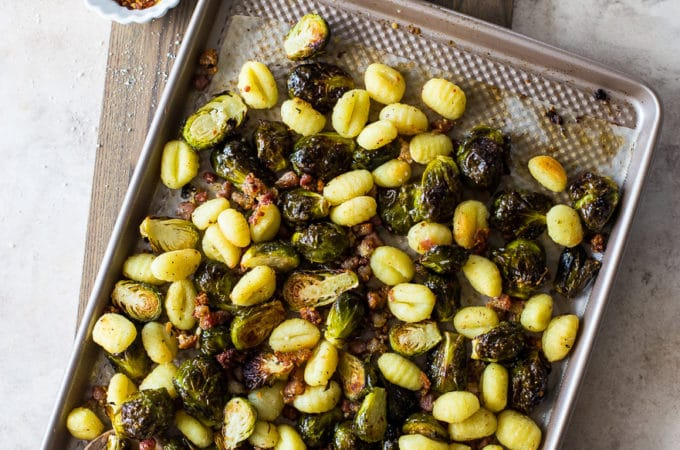 Overhead photo of a sheet pan meal with brussels sprouts, gnocchi and pancetta
