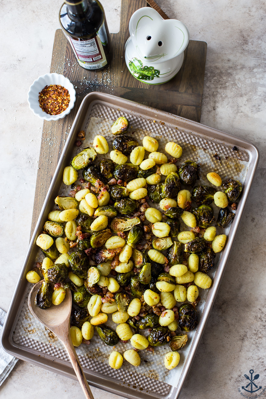 Overhead photo of a brussels sprouts sheet pan meal on a wooden board