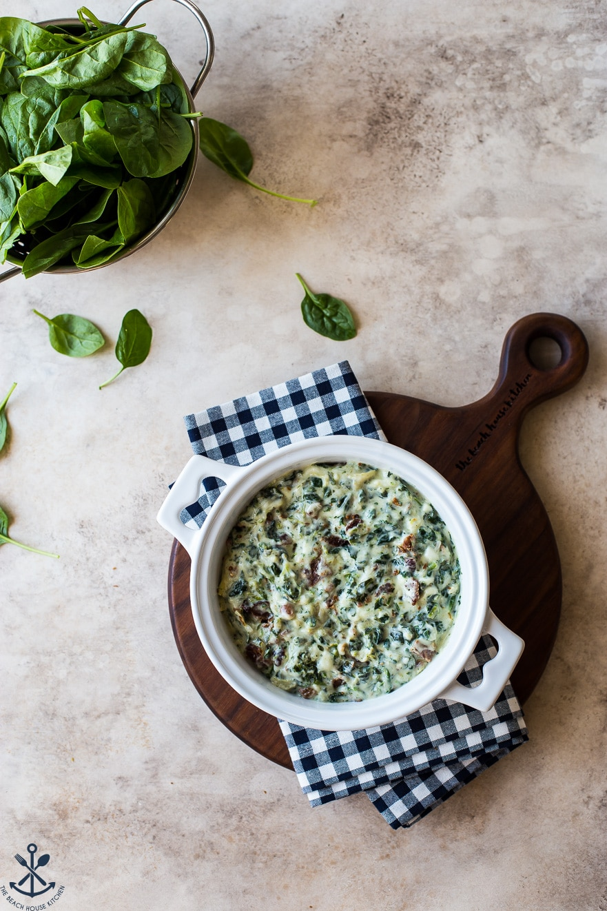 Overhead photo of pre-baked spinach dip in a white baking dish on a wooden board with a bowl of spinach leaves off to the side