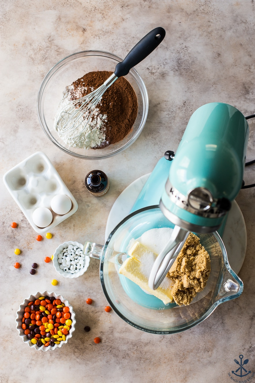Overhead photo of a turquoise mixer with brown sugar and butter, eggs, a bowl of candy, a bowl of googly eyes and a bowl of flour/cocoa mixture with a whisk