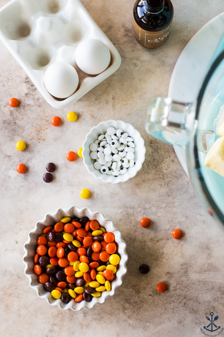 Overhead photo of a bowl of Reese's Pieces candy, a bowl of googly eyes eggs and vanilla extract bottle