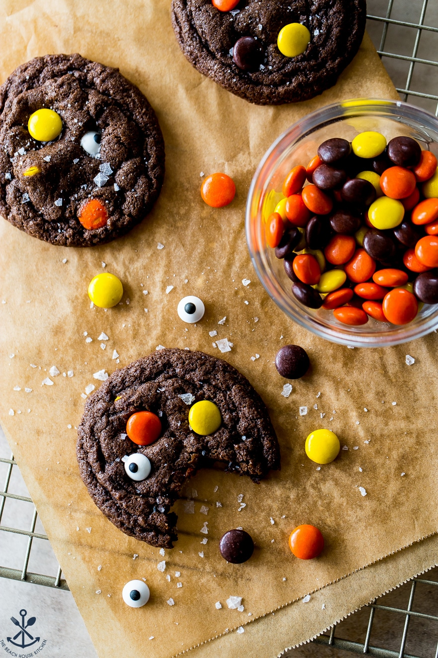 Overhead photo of chocolate cookies with Reese's Pieces and googly eyes and a bowl of Reese's Pieces candies