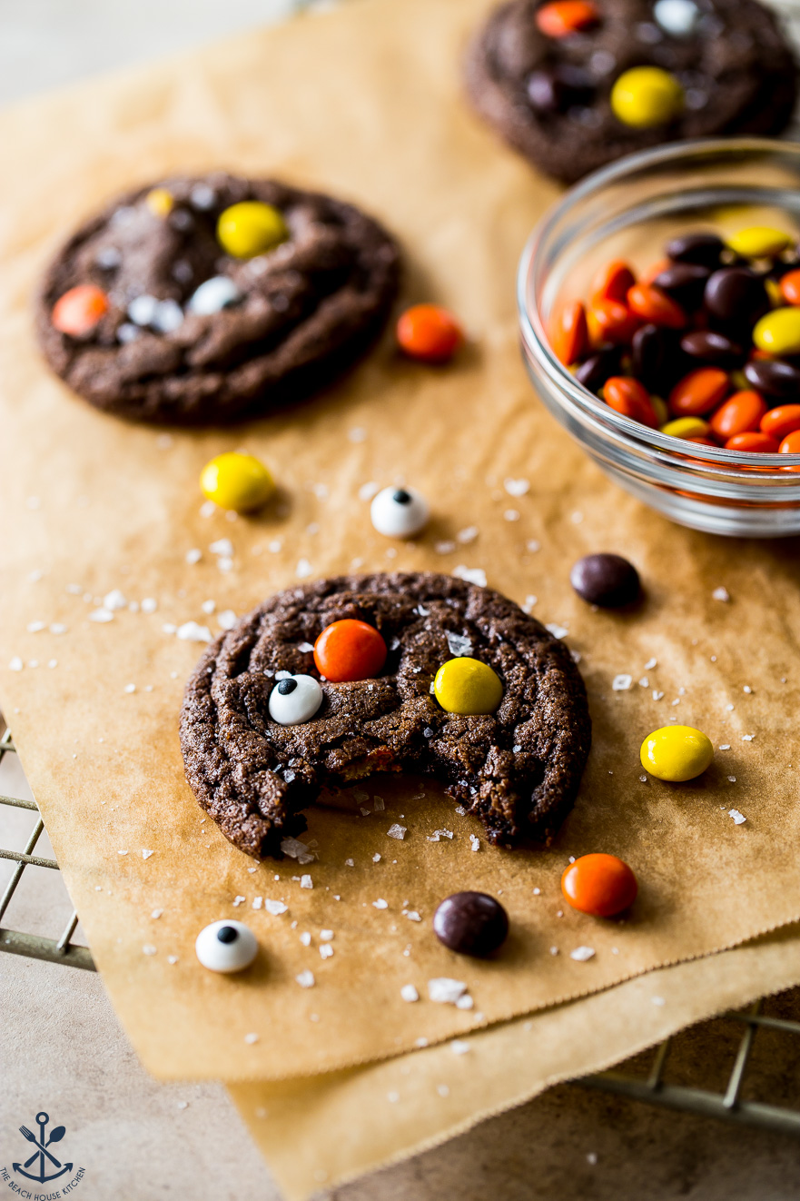 A chocolate cookie studded with Reese's pieces and googly eyes on parchment paper with a bowl of candy in the background