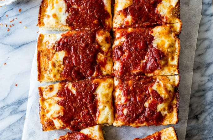 Overhead photo of a pizza cut into squares on a marble board
