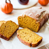A loaf of pumpkin bread with a maple glaze with two slices